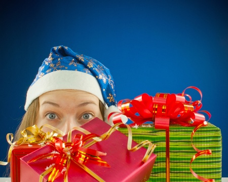 Surprised teen girl looking from behind the Christmas presents photo