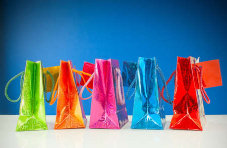 Row of colorful bags against blue background photo