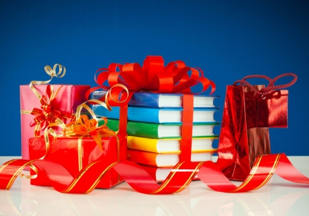 book bag: Christmas presents with stack of books against blue background Stock Photo