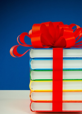 Stack of colorful books tied up with red ribbon photo