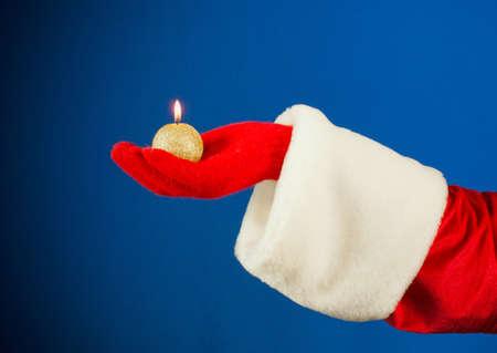 Santas hand holding a burning candle photo