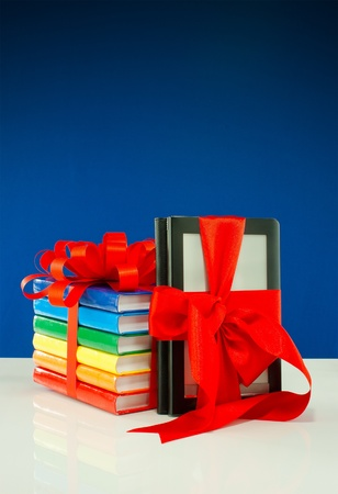 Books tied up with ribbon and electronic book reader against blue background Stock Photo - 11791194