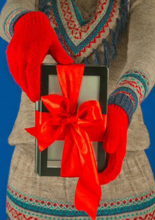 Girl holds electronic book reader with red gloves photo