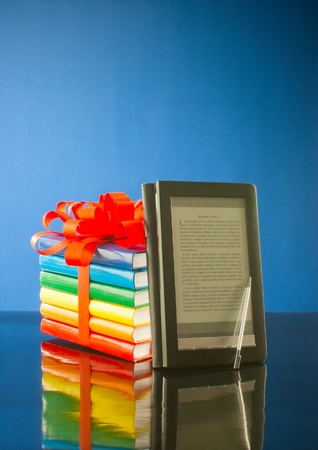 Stack of books with electronic book reader against blue background photo