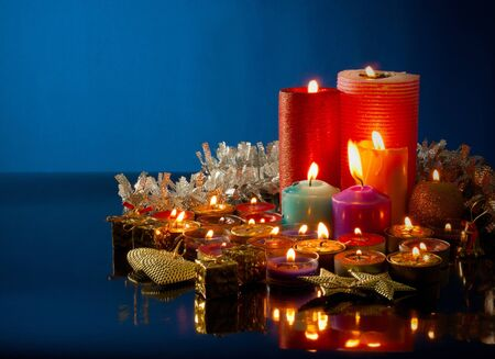 A lot of burning colorful candles against dark blue background photo