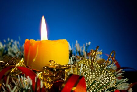 Burning candle with Christmas decorations against blue background photo
