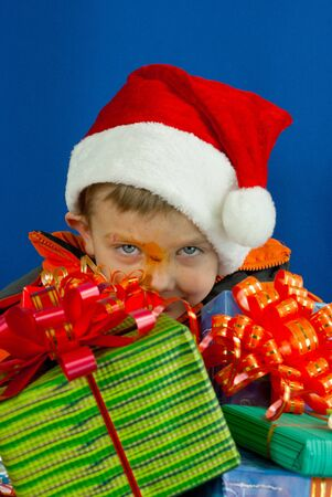 Surprised boy looking from behind the Christmas presents photo