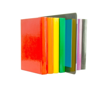 Row of colorful books and electronic book reader over white background photo