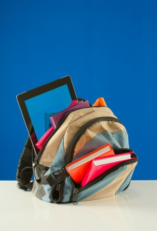 Backpack with colorful books and tablet PC on the blue background photo