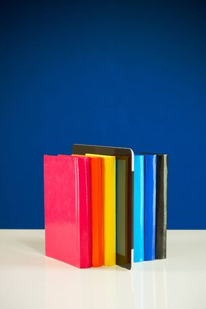 Row of colorful books and tablet PC over blue background photo