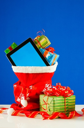 Tablet PC with heap of presents in red bag against blue background Stock Photo - 11885526