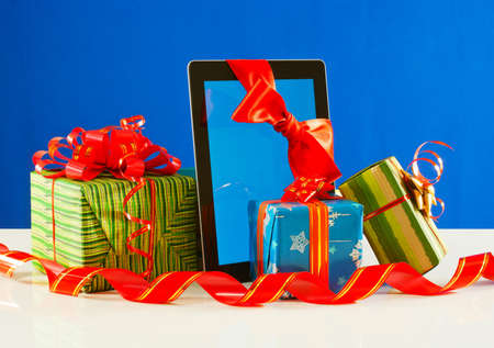 Presents with a tablet pc against blue background photo