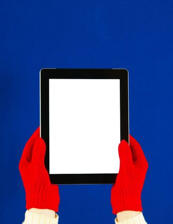 Hands wearing red gloves holding a tablet PC Stock Photo