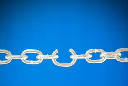 Steel chain with a broken link over blue background photo