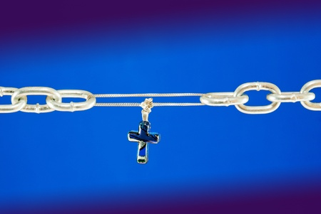 Broken chain connected with a cross - metaphor of Christs salvation