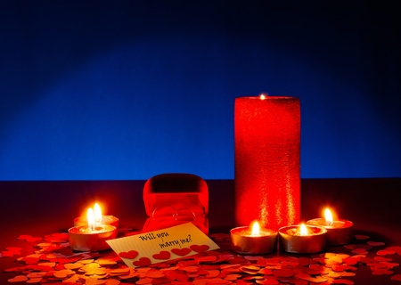 Two rings and a card with marriage proposal with six candles on the blue background