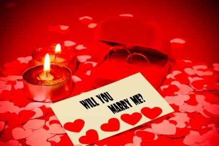 Card with marriage proposal and two rings and two candles over red background photo