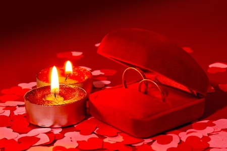 Two rings in a box and two candles over red background