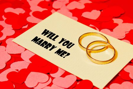 Two rings and a card with marriage proposal on the red background