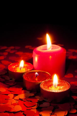 Four burning candles over red background with heart shapes photo