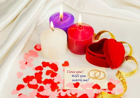 Two rings and a card with marriage proposal with three candles on the red background photo