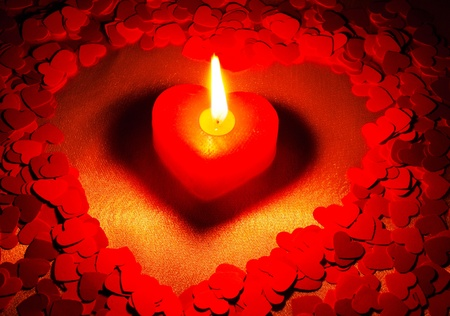 candle light: Burning heart shaped candle over red background