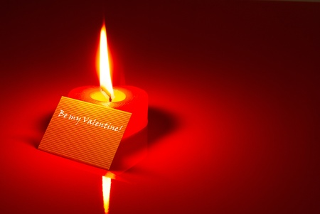 Burning heart shaped candle and a Valentines card over red background photo