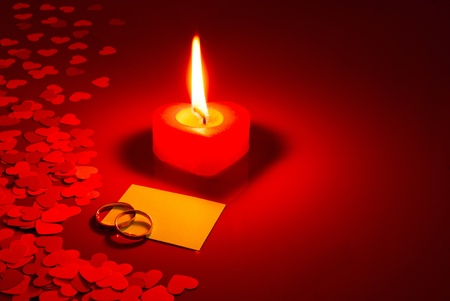 Two rings and a blank card with burning candle on red background photo