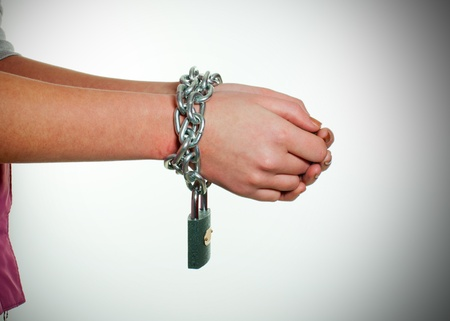 human trafficking: Hands tied up with chains against light background
