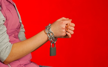 Hands tied up with chains against red background photo