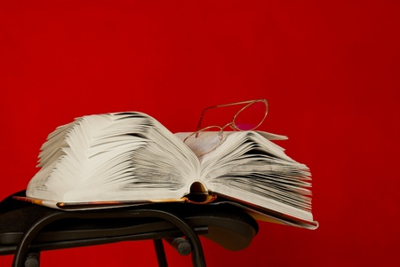 reg: Open book laying on the chair against red background Stock Photo