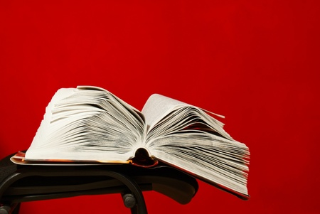 Open book laying on the chair against red background photo