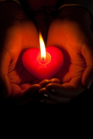 Human hands hold heart shaped burning candle against dark background Stock Photo