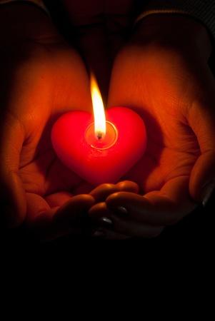 vela: Las manos humanas tienen vela en forma de coraz�n en llamas contra el fondo oscuro Foto de archivo