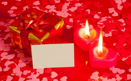 Present and two heart shaped candles with blank card photo
