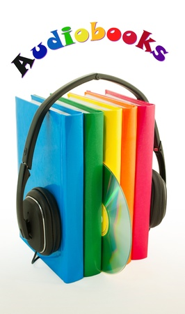 Row of books and headphones on the reflective surface over white background photo