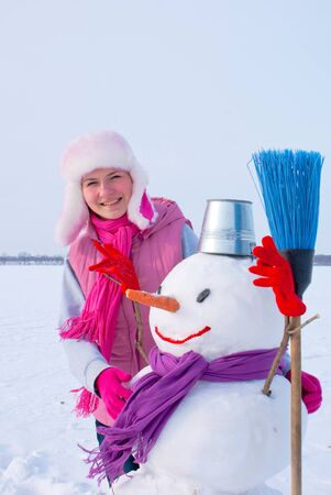 Teenage girl with snowman at winter time photo