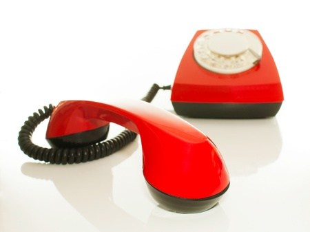 handset: Red old fashioned handset and telephone against white background. Shallow depth of field. Stock Photo