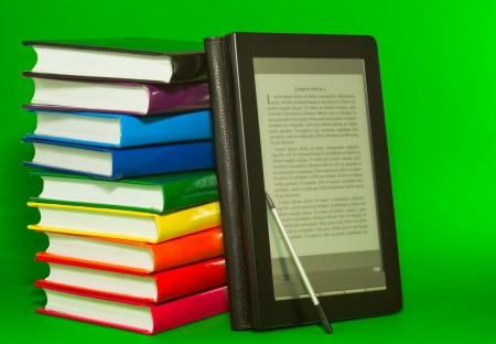 Electronic book reader with stack of printed books against green background
