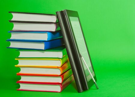 Electronic book reader with stack of printed books over green background photo