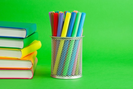 Stack of colorful books and socket with felt pens Stock Photo