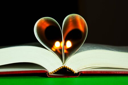Open book laying on the table with heart shaped pages photo