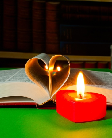 the scriptures: Open book laying on the table with burning candle