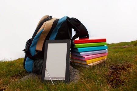 Stack of colorful books and electronic book reader on the grass Stock Photo - 12166602