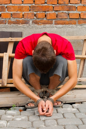 dependency: Man tied up with rope against break wall