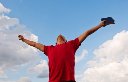 Young man staying with raised hands against blue sky Stock Photo