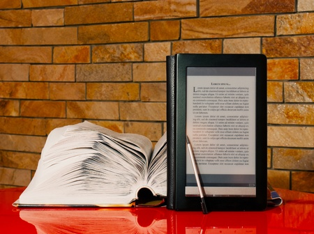 Open book and electronic book reader over brick wall Stock Photo - 12520138
