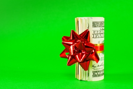 A wad of US one hundred dollar bills tied up with red ribbon over green background