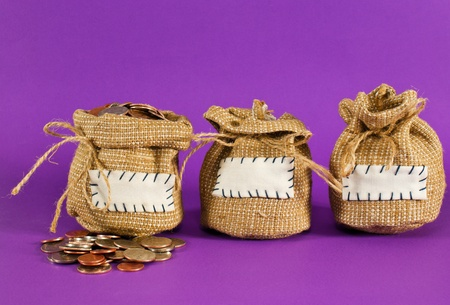 Three sacks full of coins over purple background photo