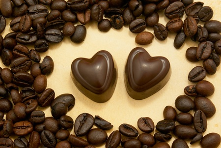 Two heart shaped chocolate candies and coffee beans on grungy paper photo